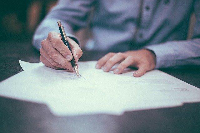 člověk, který podepisuje dokumenty