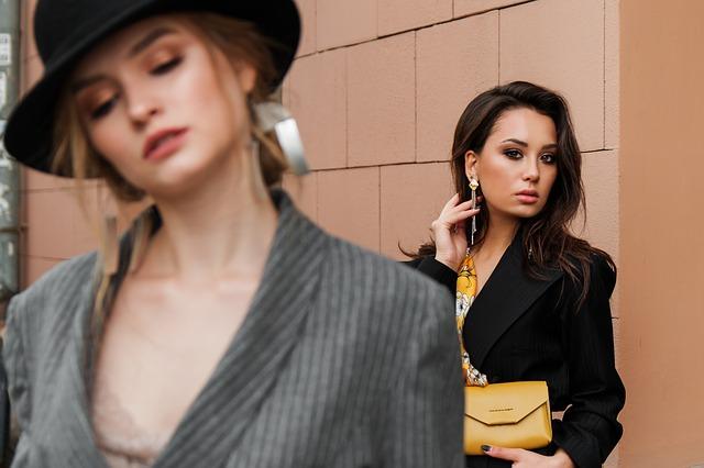 dvě stojící ženy, jedna z nich drží v rukou kabelku