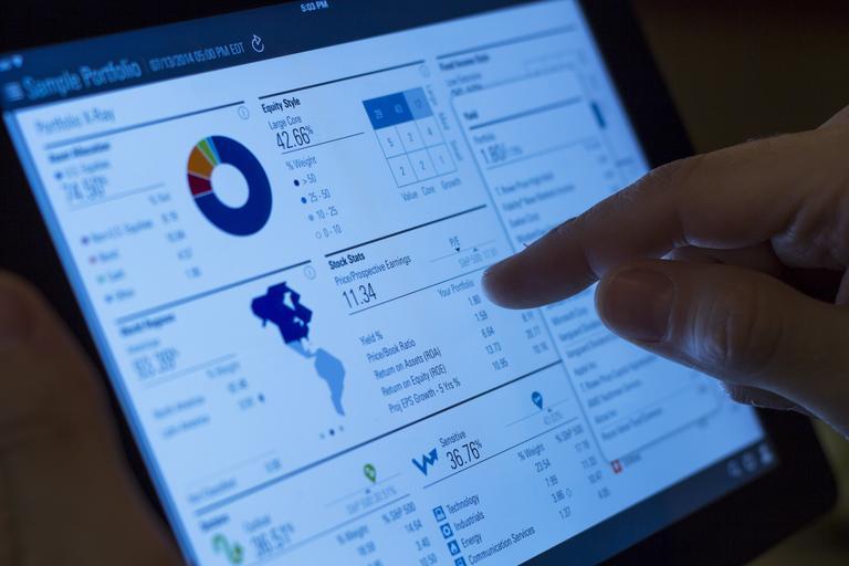 tablet, a prst ukazuje na obrazovku, tam jde vidět tabulka, čísla, grafy