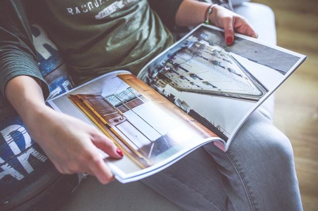 žena má na klíně časopis
