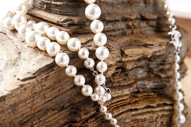 Perlový náhrdelník pověšený na kameni