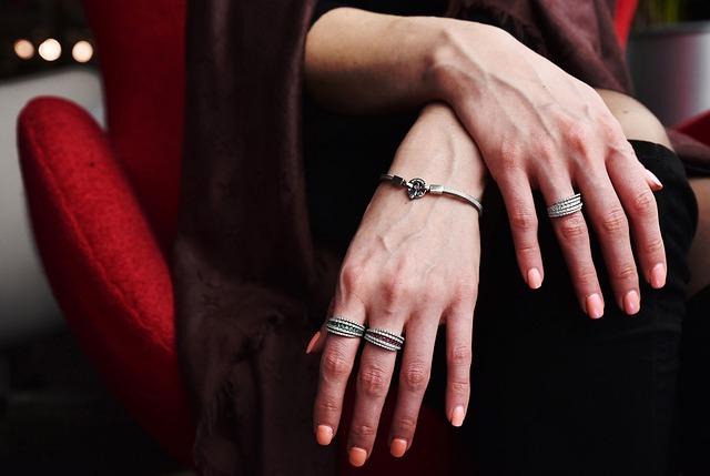 Detail ženských rukou ozdobených prsteny